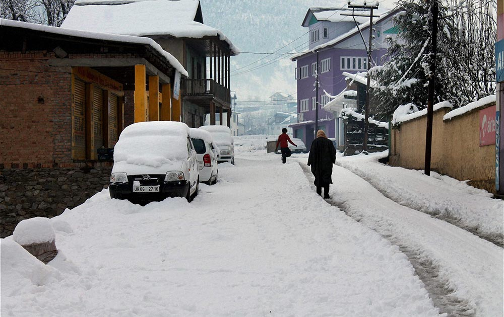 जम्मू से 200 किलोमीटर दूर भदेरवाह में भारी बर्फबारी के बीच गुजरते कुछ लोग।