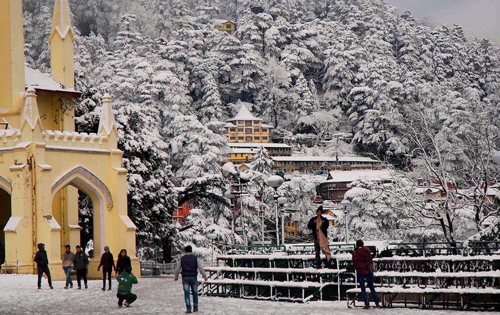 शिमला में सीजन की पहली बर्फबारी का लुत्फ उठाते हुए सैलानी।