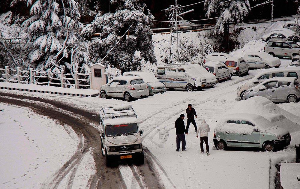 शिमला में बर्फबारी के बीच सड़क पर चलती एक कार।