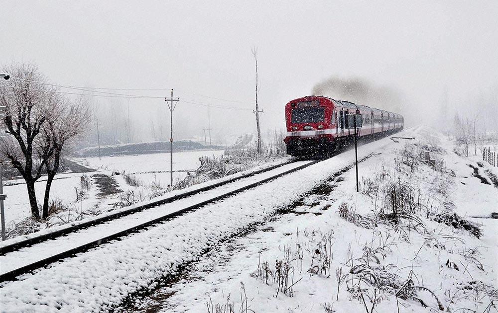 काजीगुंड में बनिहाल-बारामूला रेल लाइन के बीच भारी बर्फबारी के दौरान ट्रैक पर दौड़ती ट्रेन।