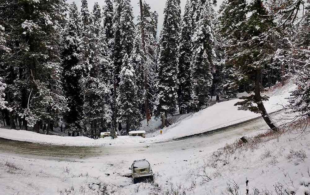 बारामूला जिले के गुलमर्ग में भारी बर्फबारी के बीच फंसी एक कार।