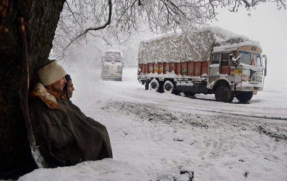 काजीगुंड में भारी बर्फबारी के बीच खड़ा एक ट्रक। पेड़ के निकट विश्राम करते श्रमिक।