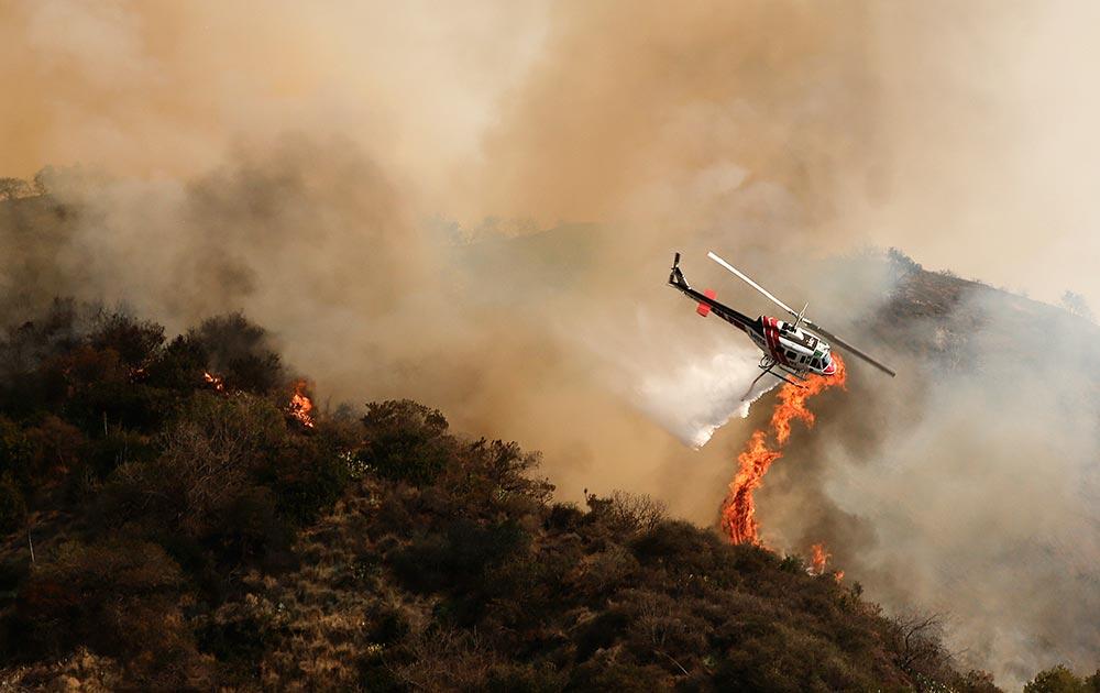 कैलिफ के जंगलों में लगी आग बुजाता हेलीकॉप्टर।
