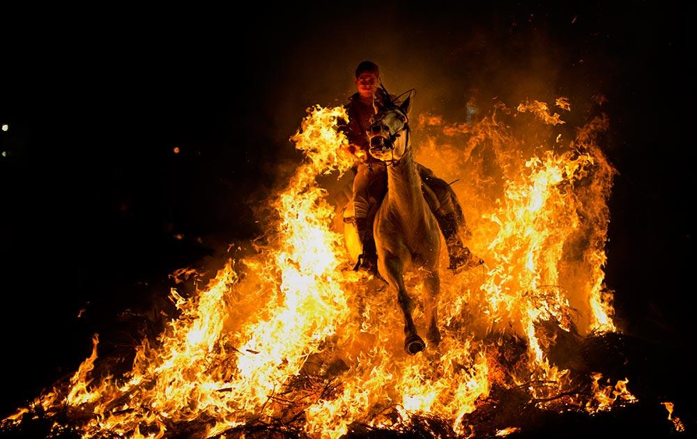 स्पेन के मैड्रिड में एक व्यक्ति आग के शोलों के बीच से गुजरता हुआ।