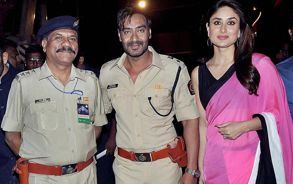 समारोह में एक पुलिस अधिकारी के साथ अभिनेता अजय देवगन और करीना कपूर।