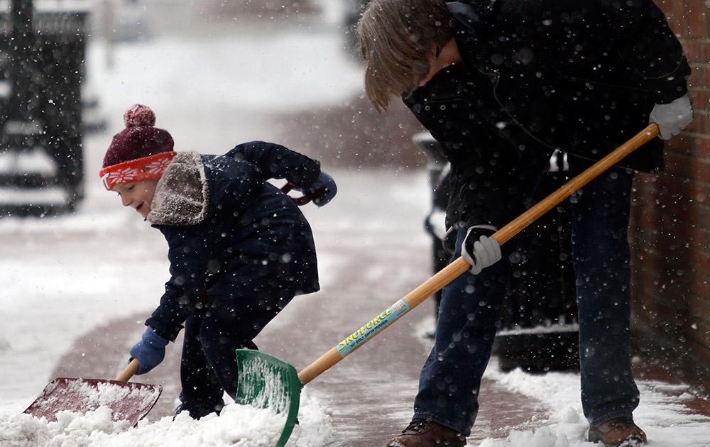 ब्लैक्सबर्ग में अपनी ग्रैंडमदर के साथ एक नन्हा बालक बर्फ को हटाते हुए।