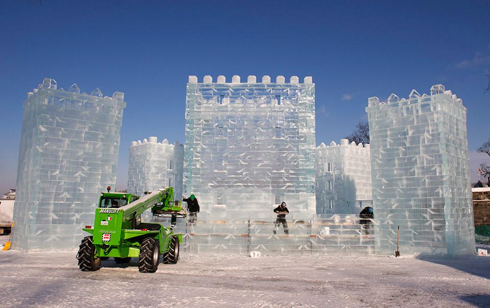 क्यूबेक सिटी में सब जीरो तापमान के बीच आइस कैसल कार्निवल को अंतिम रूप देते हुए वर्कर्स।