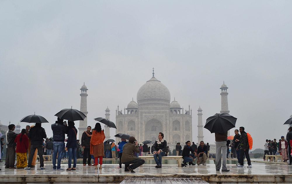 आगरा में ताजमहल के सामने बारिश से बचने का प्रयास करते हुए पर्यटक।