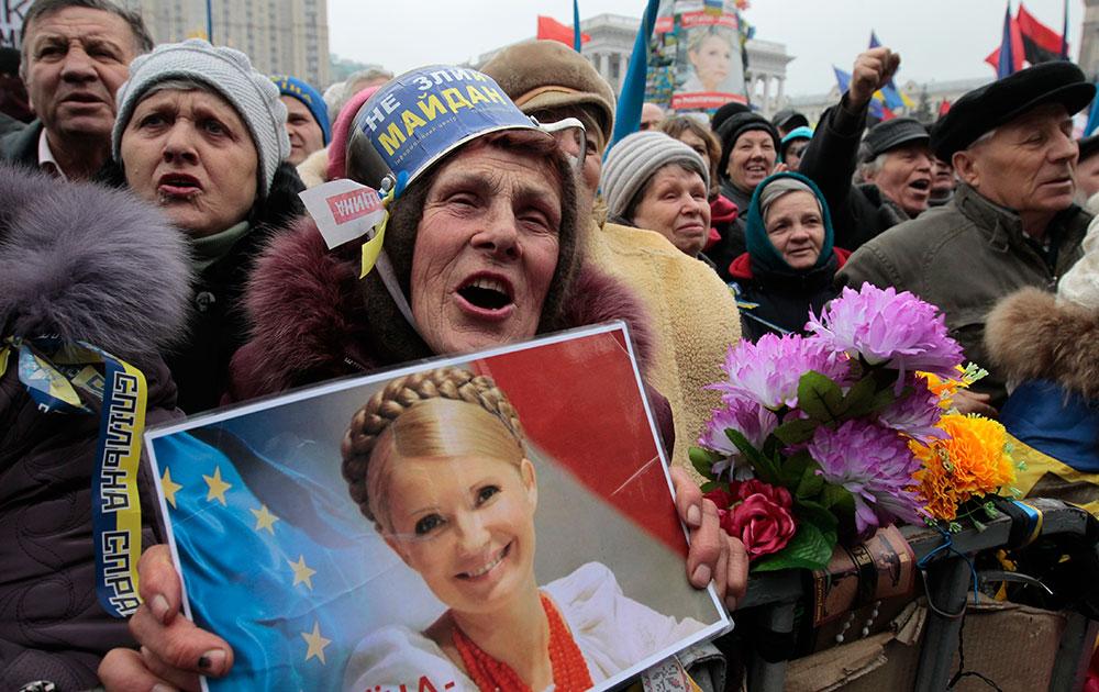 यूक्रेन के कीव में सरकार के खिलाफ प्रदर्शन करते लोग।