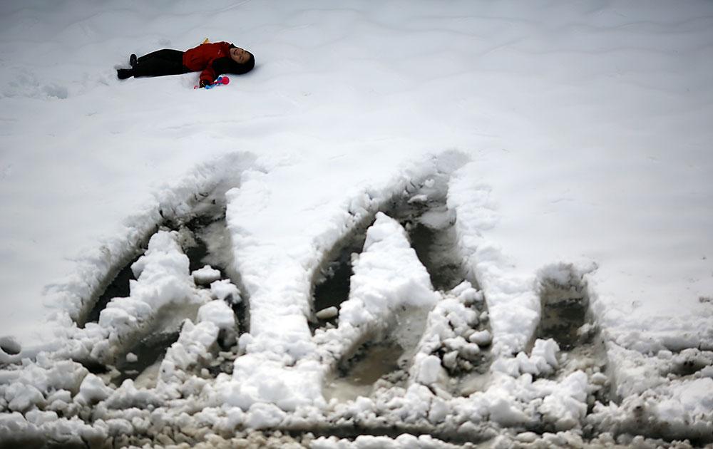 जापान के याकोहामा में बर्फ से ढंके पार्क पर खेलते बच्चे।