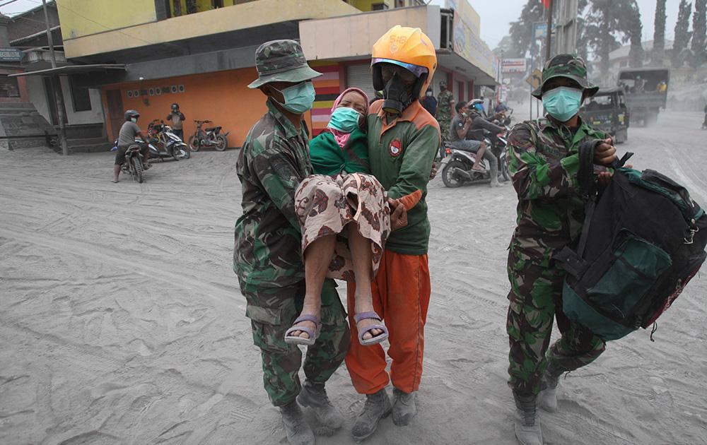 इंडोनेसिया के पूर्वी जावा के मलंग में माउंट केलुड के फटने से घायलों को ले जाते हुए पुलिसकर्मी और बचाव दल।