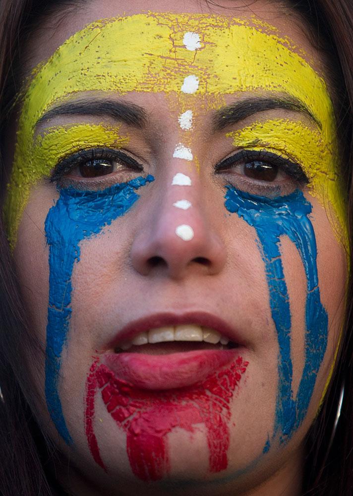 स्पेन की राजधानी मेड्रिड में वेनेजुएला सरकार के खिलाफ प्रदर्शन के दौरान वेनेजुएला के झंडे के रंगों को चेहरे पर प्रदर्शित कर प्रदर्शन करती एक महिला।
