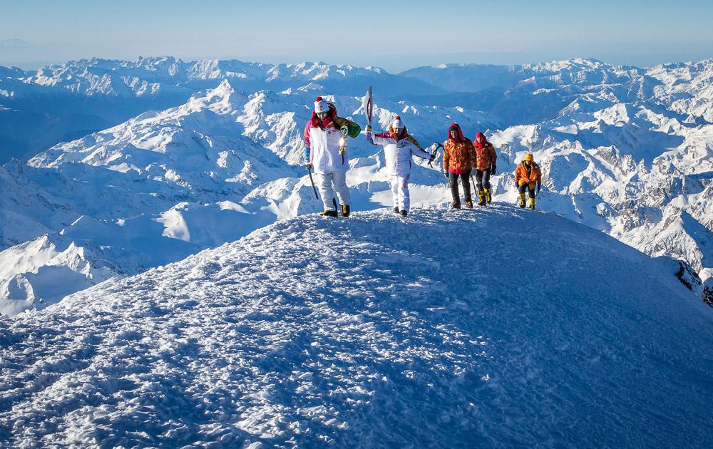 पर्वतारोही करीना मेजोआ केसाथ कुछ पर्वतरोही ओलंपिक टार्च लेकर रूस की पर्वत पर चढ़ाई करते हुए।
