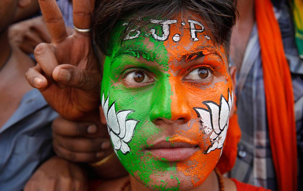 इलाहाबाद में नरेंद्र मोदी की एक रैली में अपने चेहरे के जरिए बीजेपी का समर्थन करता एक कार्यकर्ता।