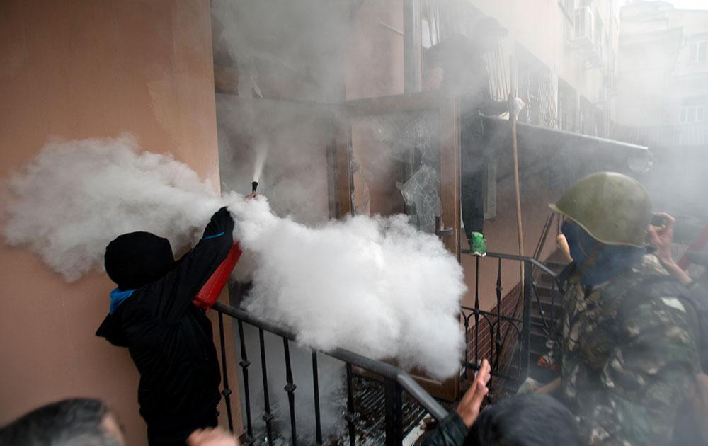 यूक्रेन में प्रदर्शनकारियों पर पुलिस आंसू गैस के गोले फेंकती हुई।