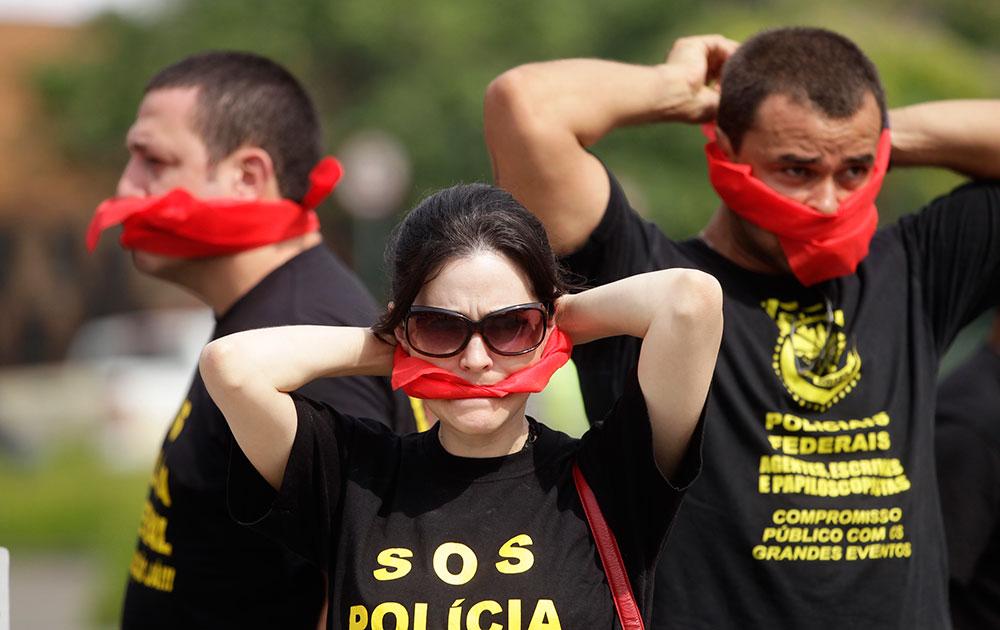 ब्राजील में होनेवाले फुटबॉल वर्ल्ड कप से पहले फेडरल पुलिस के सुरक्षा कर्मी संदेश देते हुए।