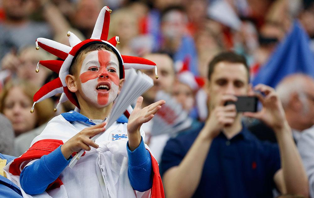 लंदन में इंग्लैंड एवं पेरू के बीच फुटबाल मैच का लुत्फ उठाते लोग।