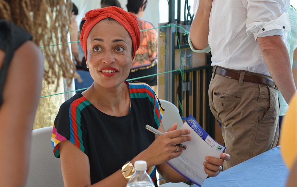 जमैका में अपने प्रशंसक के लिए पुस्तक पर अपना ऑटोग्राफ देतीं प्रसिद्ध उपन्यास लेखिका जैदी स्मिथ।