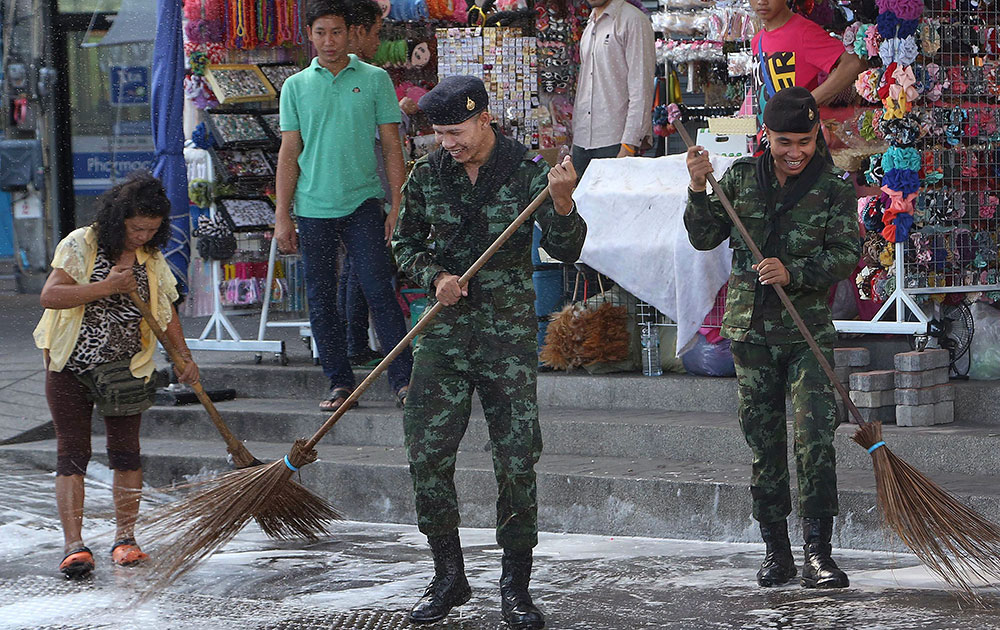 बैंकाक में विक्टरी स्मारक के पास सफाई करते सेना के जवान एवं स्थानीय लोग।