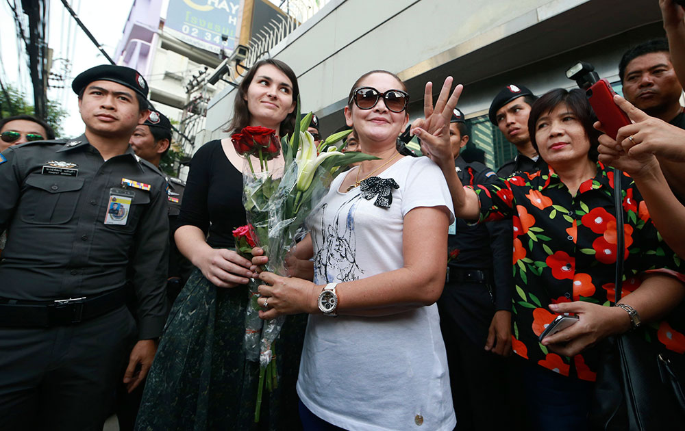 थाईलैंड की राजधानी बैंकॉक में ऑस्ट्रेलिय दूतावास के बाहर प्रदर्शन करते प्रदर्शकारियों से फूलों का गुच्छ स्वीकार करतीं दूतावास की अधिकारी।