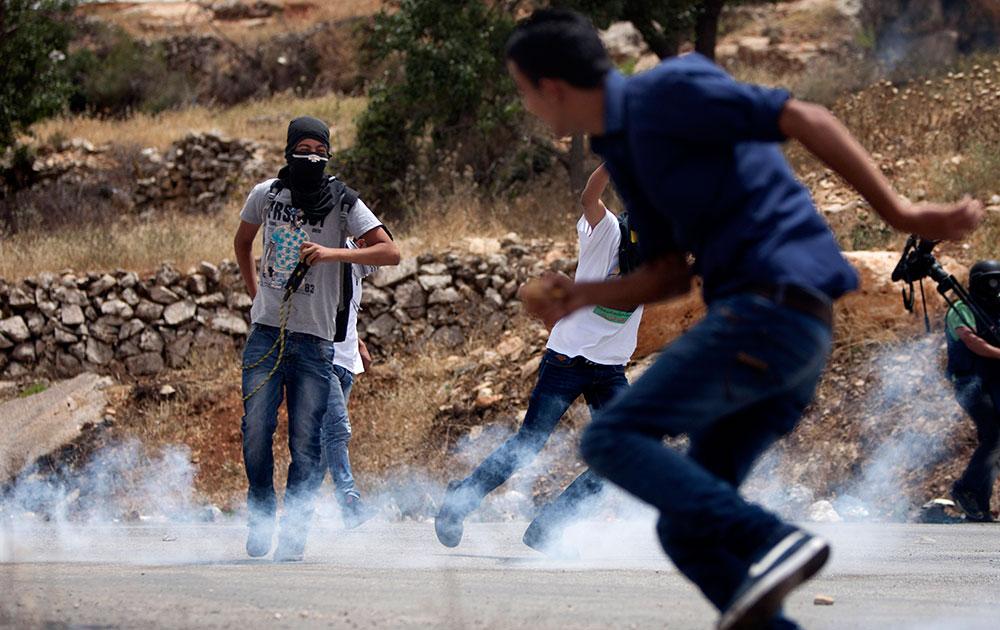 रामाल्ला के वेस्ट बैंक सिटी के नजदीक प्रदर्शन करने के दौरान इसरायली जवानों से संघर्ष के बाद छोड़े गए अश्रुगैस के गोले से खुद को बचाते प्रदर्शनकारी। ये प्रदर्शकारी इसरायली जेल में बंद फिलिस्तीनी कैदियों के 42 दिन से चले आ रहे आमरण अनशन के समर्थन में किया गया है।