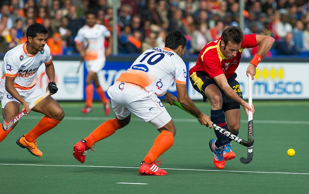 नीदरलैंड : हेग में हॉकी वर्ल्ड कप मैच के दौरान भारत के धर्मवीर सिंह के साथ बॉल को अपने कब्जे में लेने के लिए जूझते हुए स्पेन के डेविड एलिग्रे।