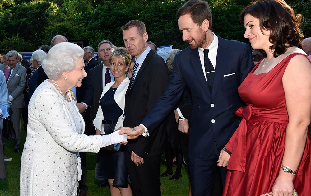 टूर डी फ्रांस के विजेता ब्रेडले विगिंस से हाथ मिलाती हुईं ब्रिटेन की क्वीन एलिजाबेथ द्वितीय।
