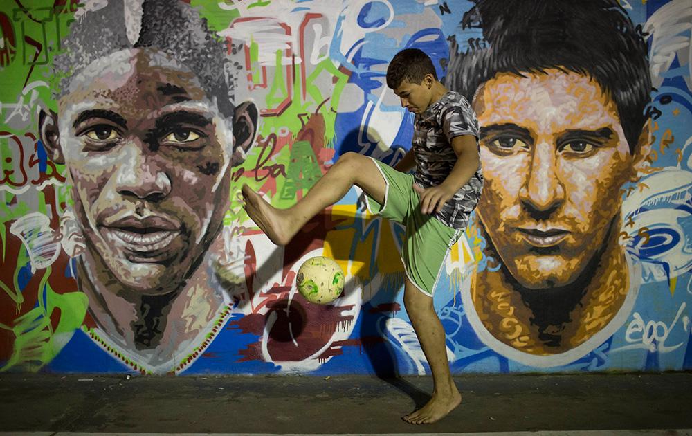 ब्राजील के रियो डी जेनेरियो स्थित एक स्लम में फ्री स्टाइल सॉकर में मशगूल एक बालक।