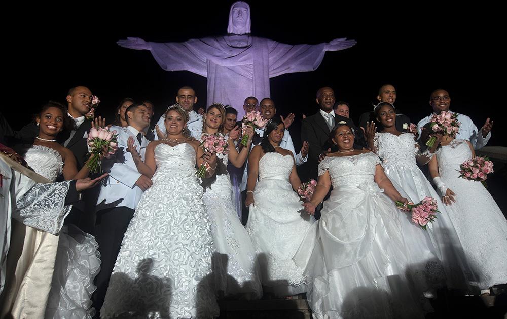 ब्राजील के रियो डी जेनेरियो में सामूहिक विवाह के बाद क्राइस्ट टी रीडीमर स्टेट्यू के निकट पोज देते हुए नवविवाहित जोड़े।