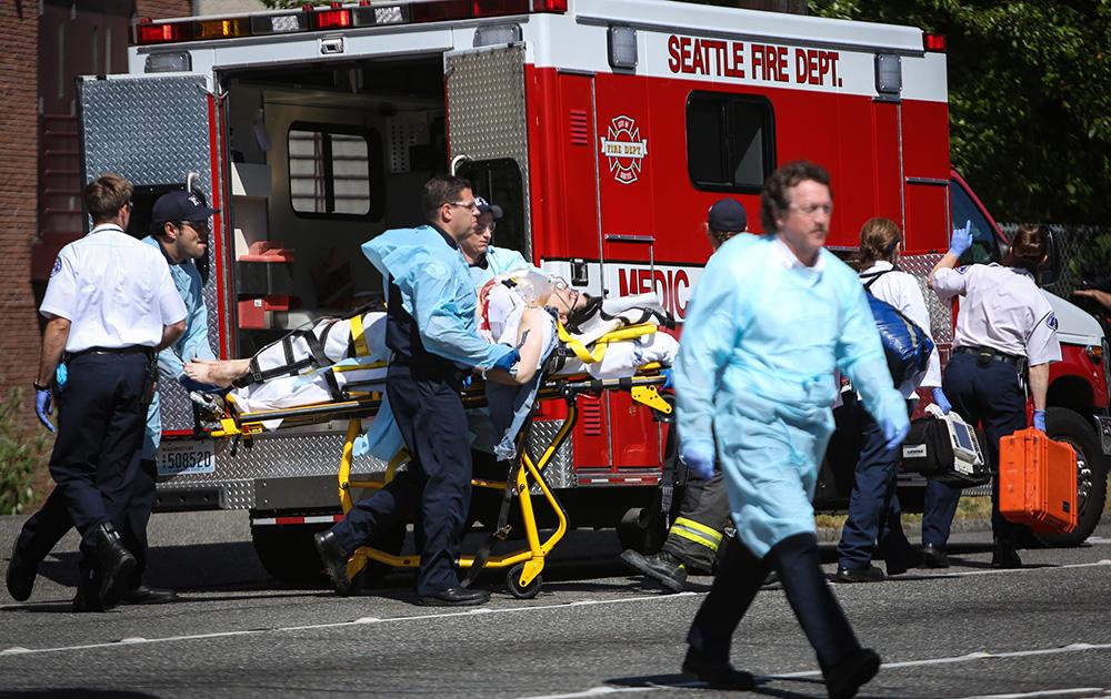 अमेरिका: सिएटल में सिएटल पेसिफिक यूनिवर्सिटी के निकट एक व्यक्ति को गोली लगने के बाद उसे चिकित्सा सहायता पहुंचाते मेडिकल कर्मी।