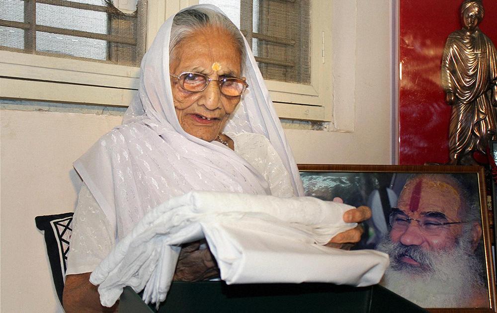 पाकिस्तान के प्रधानमंत्री नवाज शरीफ की ओर से भेंट की गई साड़ी को देखते हुए प्रधानमंत्री नरेंद्र मोदी की मां हीराबा।