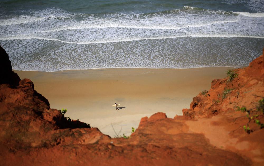 ब्राजील के नैतमिया बीच पर सर्फिंग के लिए तैयारी करता एक व्यक्ति।