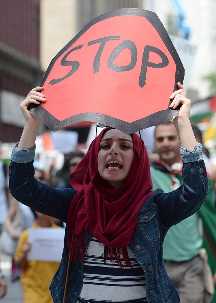 ओटावा में इजराइल और हमास में चल युद्ध के खिलाफ प्रदर्शन करती युवती।