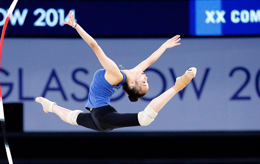 स्काटलैंड: ग्लासगो में कॉमनवेल्थ गेम्स 2014 के आगाज से पहले रिदमिक जिमनास्टिक का अभ्यास करती एक एथलीट।