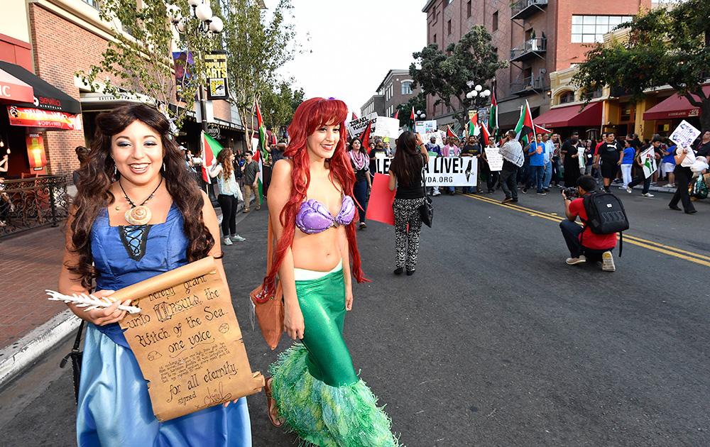सैन डिएगो में आयोजित हास्य कोन इंटरनेशनल कन्वेंशन सेंटर के बाहर फिलिस्तीनियों के समर्थन में प्रदर्शन करते लोग।