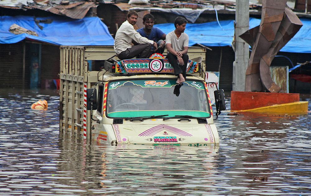 गुजरात के अहमदाबाद में लगातार कई दिनों से हो रही बारिश के बाद कई इलाकों में बाढ़ का नजारा।