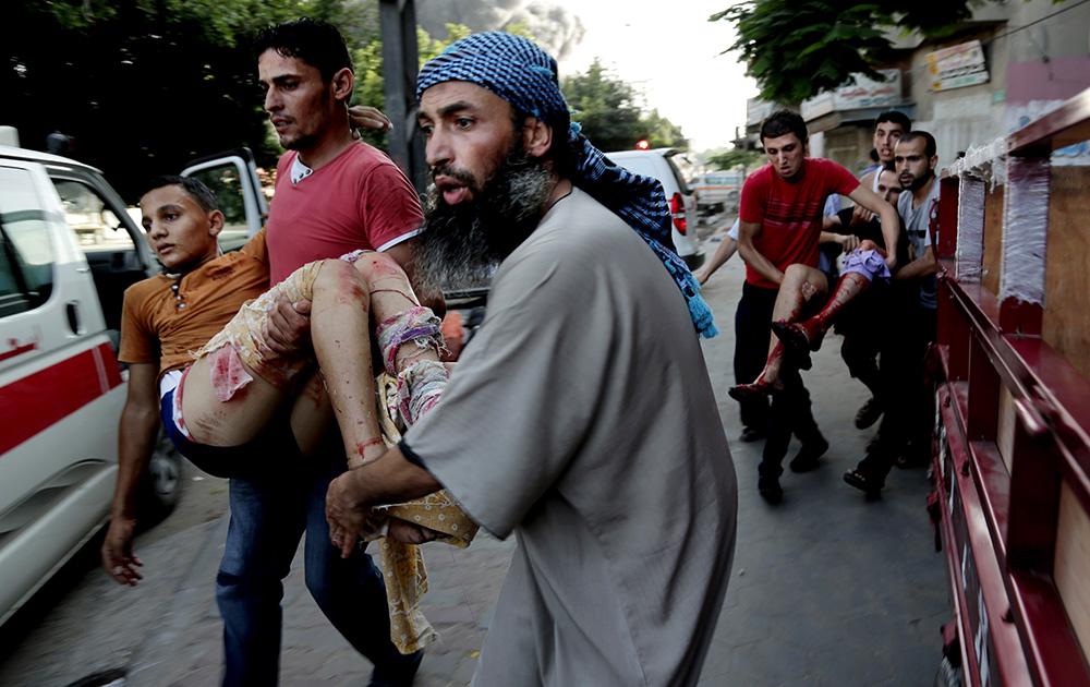 गाजा में इजरायल के हमले के बाद घायल एक बच्चे को लेकर जाते लोग।
