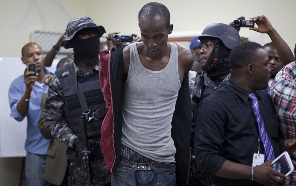 हैती के पोर्ट-ओ-प्रिंस में गिरफ्तारी के बाद पुलिस के साथ टॉसिएंट रिचर्ड्सन।