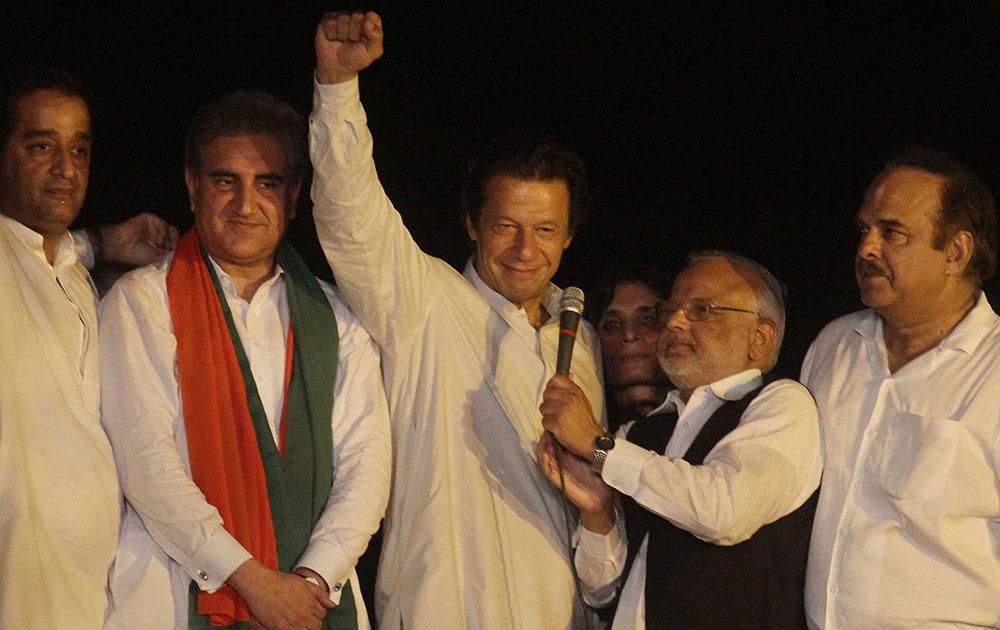 पाकिस्तान के लाहौर में अपने समर्थकों को संबोधित करते क्रिकेटर से राजनेता बने इमरान खान (बीच में)।