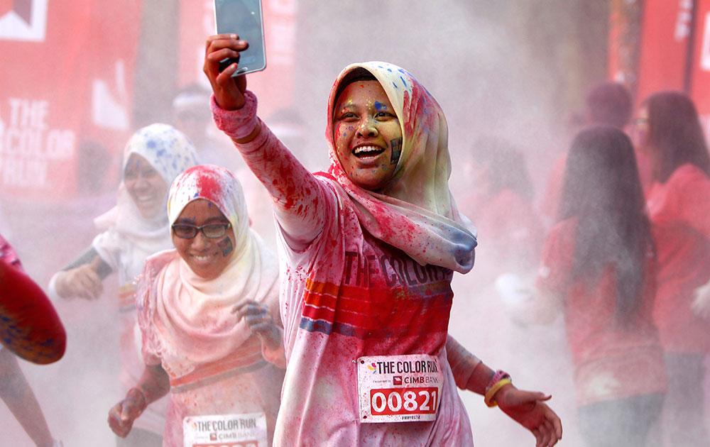 मलेशिया के कुआलालंपुर में फाइव किलोमीटर कलर रन के दौरान सेल्फी लेती हुई युवती।