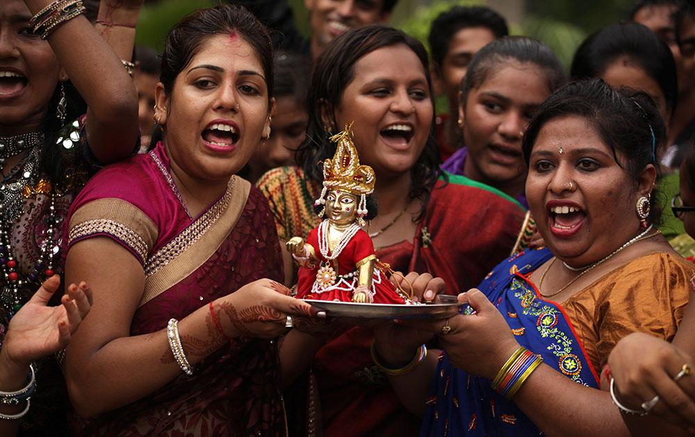 अहमदाबाद में एक स्कूल में महिला शिक्षक जन्माष्टमी के मौके पर भगवान कृष्ण की पूजा करती हुईं।