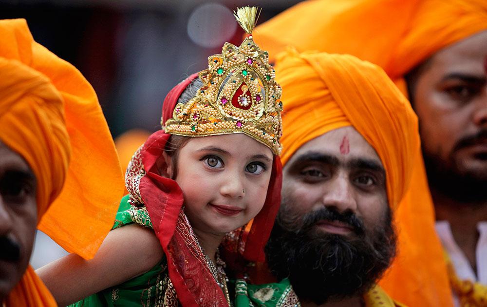 जम्मू में जन्माष्टमी उत्सव के मौके पर राधा के पोशाक में बच्ची।