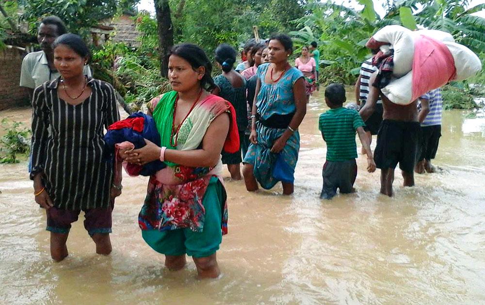 नेपाल के पश्चिमी हिस्से बर्डिया में बाढ़ आने के बाद गांववासी सुरक्षित स्थानों की ओर जाने का प्रयास करते हुए।