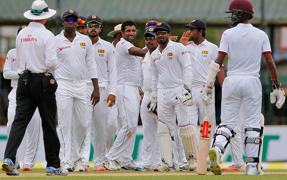 श्रीलंका के कोलंबो में दूसरे टेस्ट मैच के दौरान वेस्ट इंडीज के डेरेन ब्रावो के आउट होने के बाद धम्मिका प्रसाद को बधाई देते श्रीलंकाई क्रिकेट टीम के साथ खिलाड़ी।