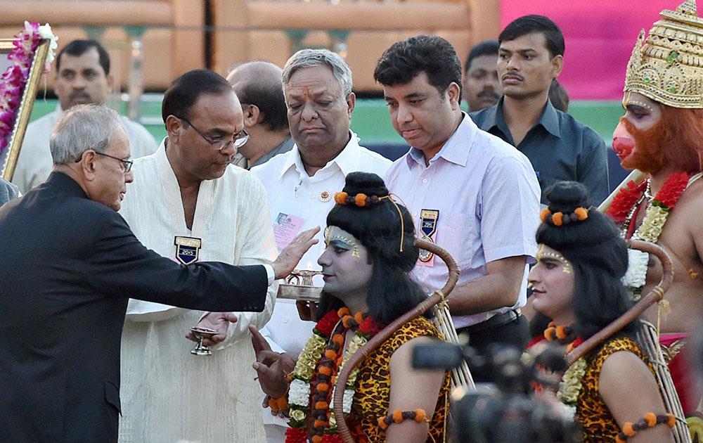 नई दिल्ली के परेड ग्राउंड में दशहरा उत्सव के दौरान भगवान राम और लक्ष्मण की भूमिका निभा रहे कलाकारों के साथ राष्ट्रपति प्रणब मुखर्जी।