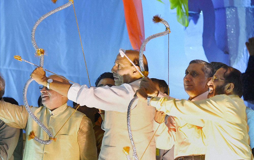रामलीला ग्राउंड में दशहरा उत्सव के दौरान अपने हाथ में तीर-धनुष थामे हुए गृह मंत्री राजनाथ सिंह।