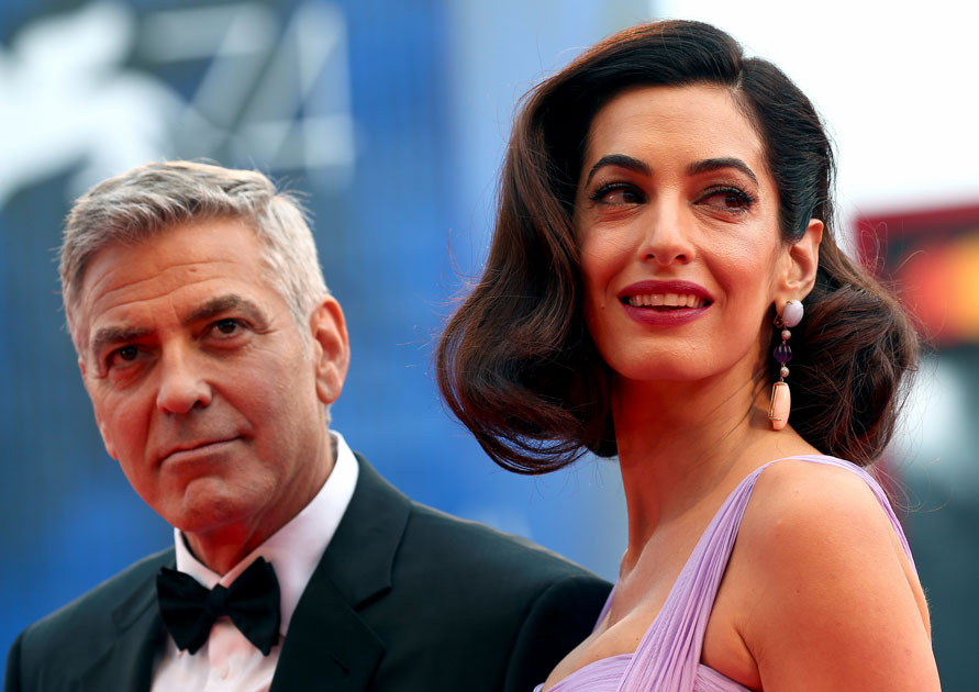 Actor and director George Clooney and his wife Amal pose during a red carpet