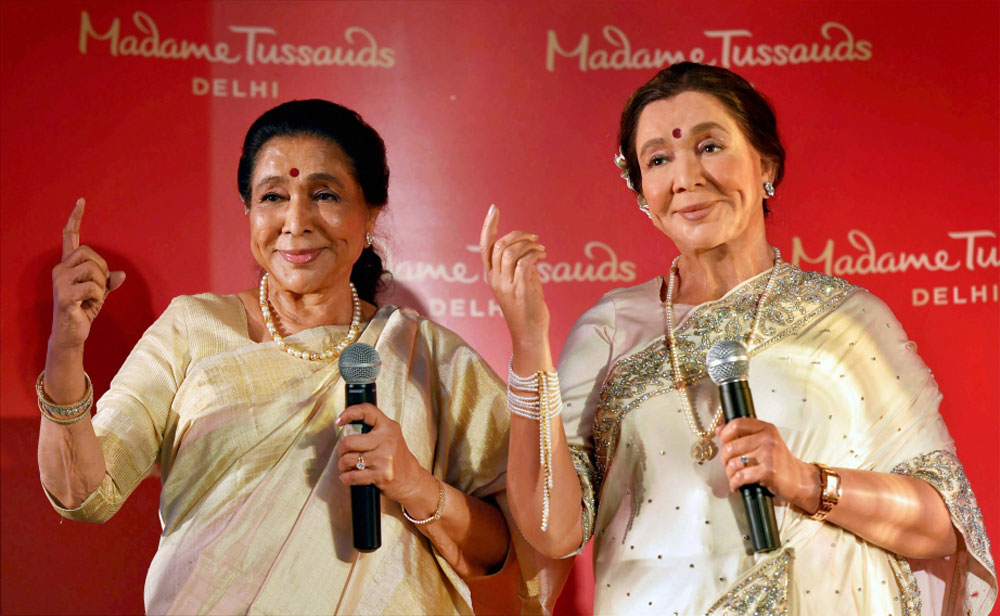 Legendary singer Asha Bhosle poses with her wax-statue during its unveiling, in New Delhi.