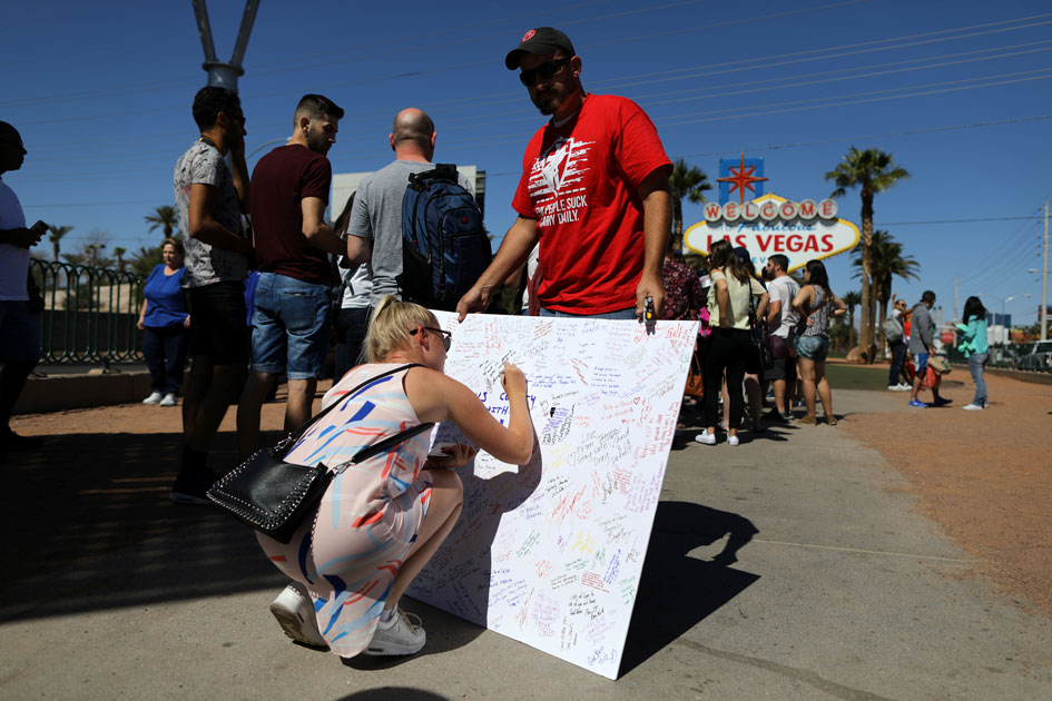 A woman signs a memorial board on the Las Vegas Strip for victims of the Route 91 music festival mass shooting next to the Mandalay Bay Resort and Casino in Las Vegas.