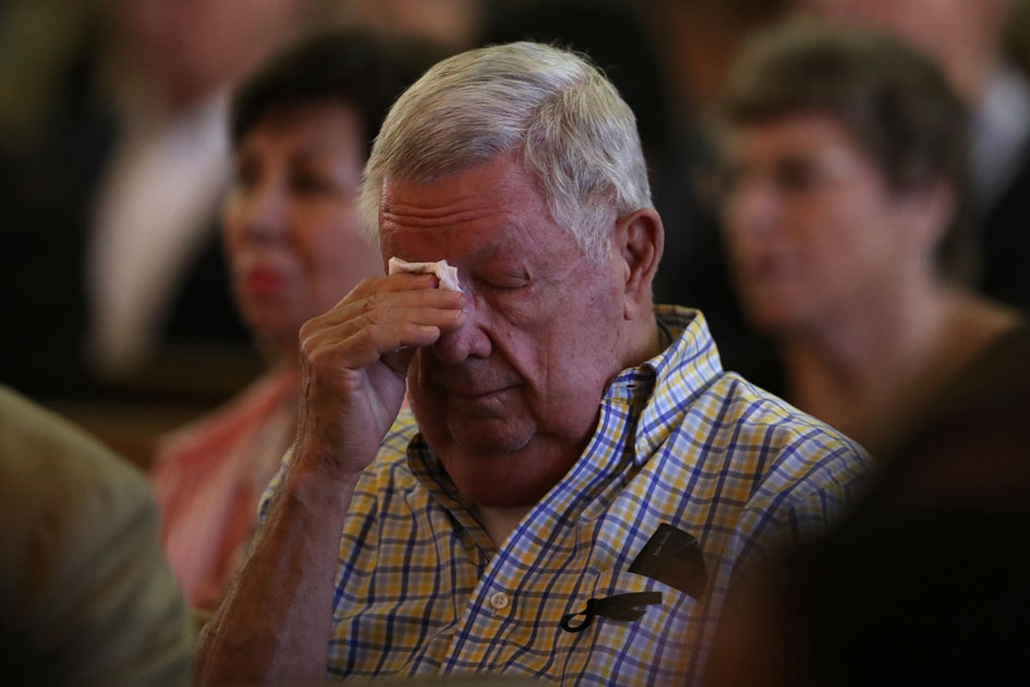 People mourn during an interfaith memorial service for victims of the Route 91 music festival mass shooting outside the Mandalay Bay Resort and Casino in Las Vegas.